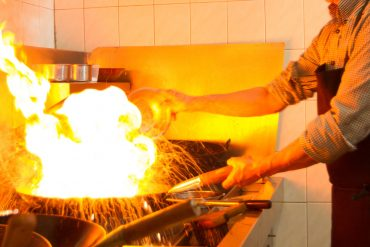 Asian restaurant chef cooking food in a wok